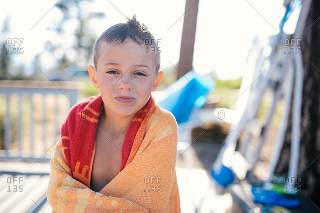Boy wrapped in towel in rural yard
