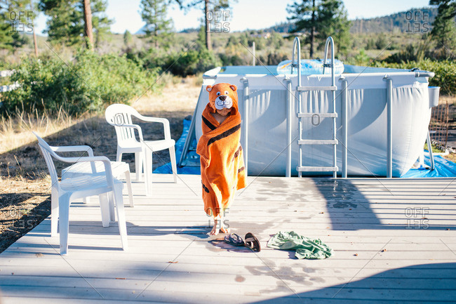Boy in hooded animal towel by pool