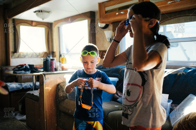 Kids putting on goggles in camper