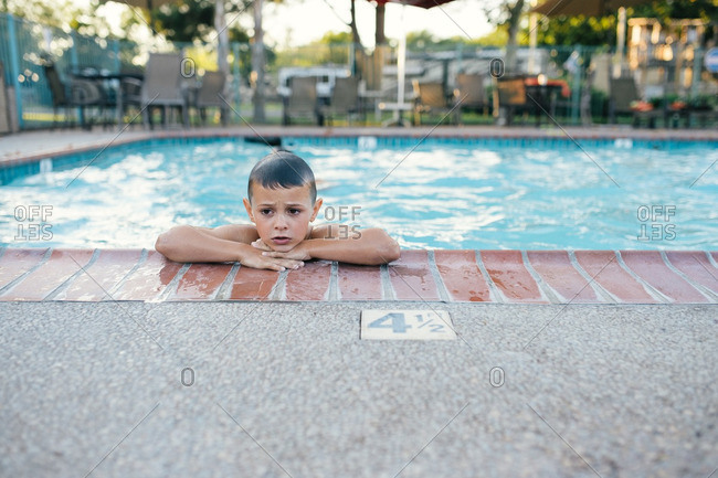 Boy resting at edge of pool