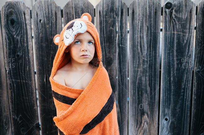 Boy in hooded towel by fence