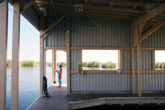 Boy fishing from a boathouse