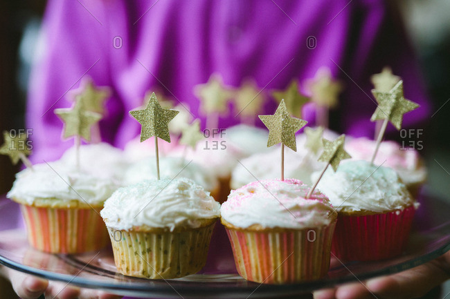 Person holding star decorated cupcakes