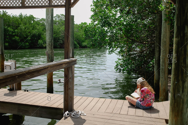 Girl reading book on a lake dock