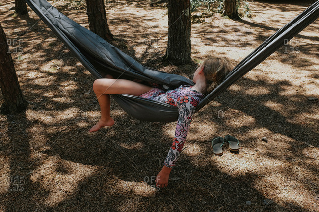 Girl lounging in hammock in forest