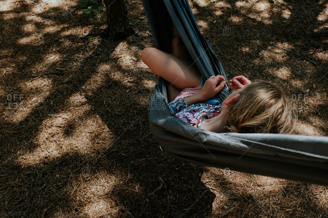 Girl lounging in hammock in woods