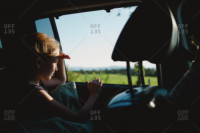 Girl staring out car window in sunlight