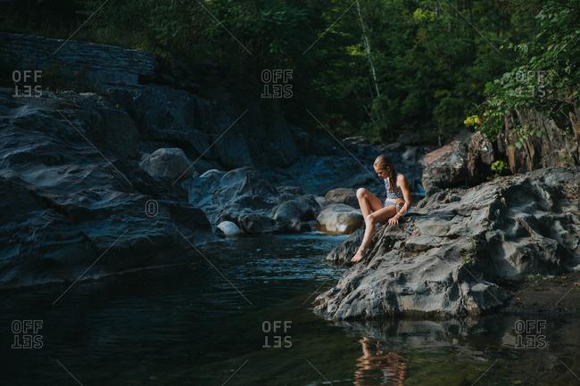 Girl sitting alone on lake edge