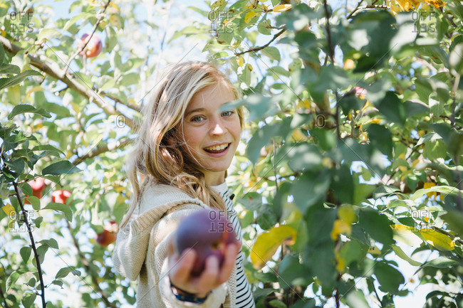 Girl among branches holding fruit