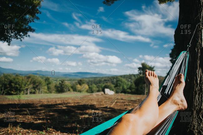Bare feet in hammock in rural setting