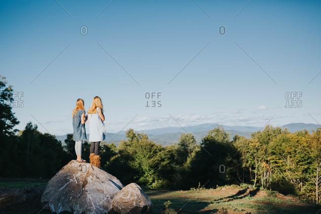 Girls on boulder over scenic vista