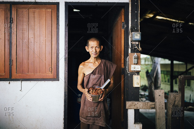 8/9/2016: A monk holds out one of the countless ingredients in Tham Krabok's drug rehab elixir, which induces vomiting in the patients at the temple.