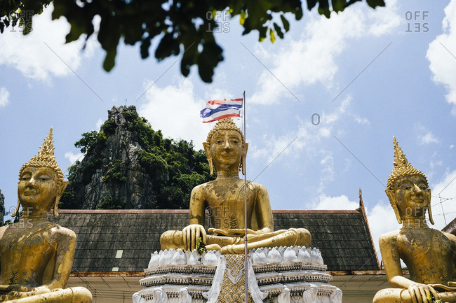 Three golden Buddhas sit sentry over Tham Krabok temple in Saraburi, Thailand.