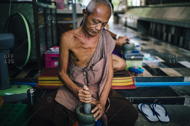 8/9/16: Monks bash herbs and roots into medicine at Tham Krabok temple in Saraburi, Thailand. Aside from drug rehab, the temple also makes other herbal concoctions that are much less poisonous to the body.