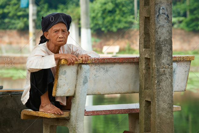 Hanoi, Vietnam - July 13, 2016: Elderly woman sitting on a bench in the park