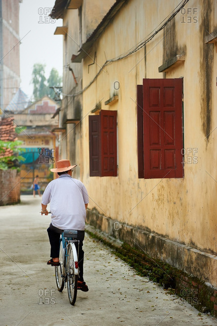 Elderly man riding a bicycle down an alley way