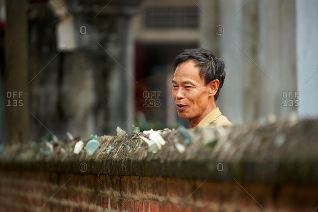 Hanoi, Vietnam - July 13, 2016: Man talking to a friend over a wall