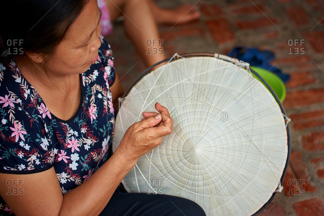 Hanoi, Vietnam - July 13, 2016: Woman sewing Vietnamese hat