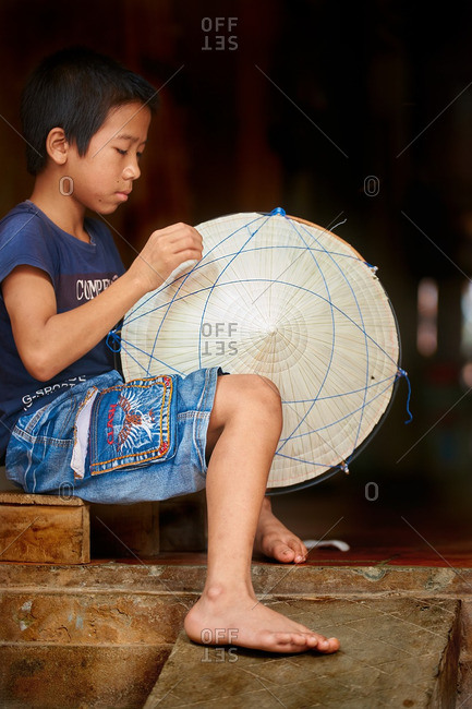 Hanoi, Vietnam - July 13, 2016: Boy making traditional Vietnamese hat.