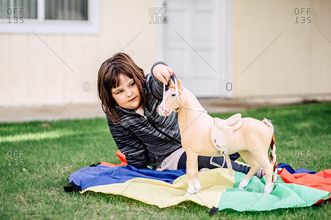Young girl playing with a toy horse