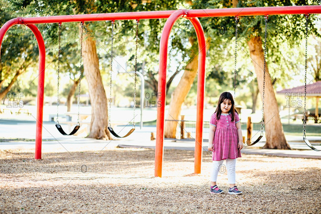 Young girl standing near a swing set