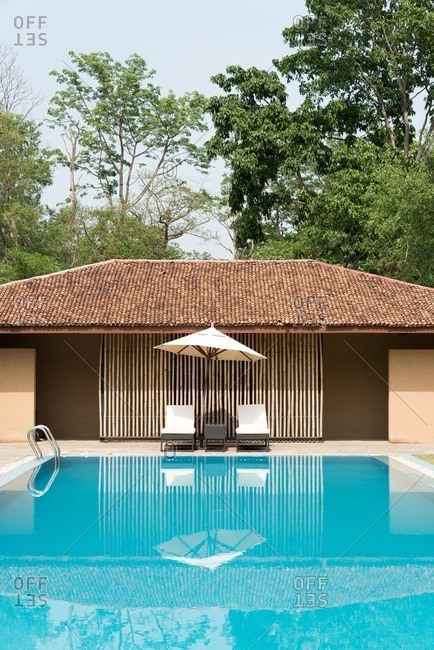 Swimming pool with lounge chairs and umbrella