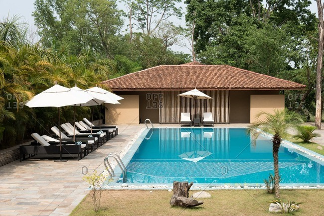 Swimming pool with lounge chairs at a resort in Nepal