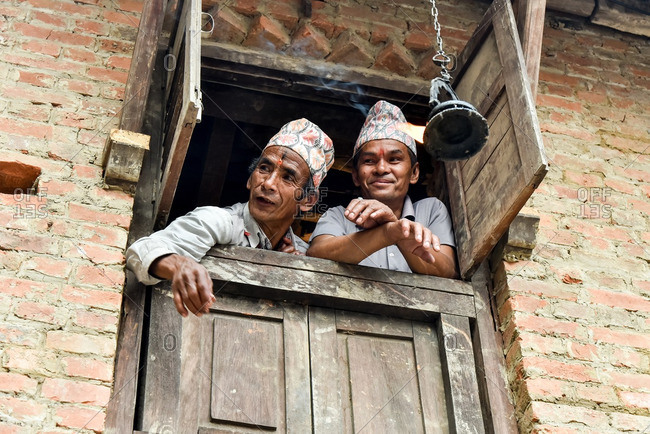 Bhaktapur, Nepal - April 12, 2016: Two Nepalese old men in a window, Bhaktapur
