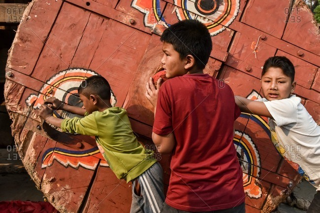 Bhaktapur, Nepal - April 13, 2016: Three kids playing with a huge a chariot during a festival in Nepal