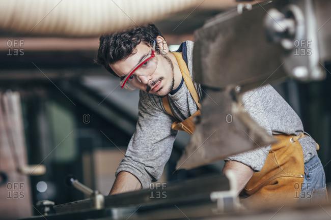 Carpenter using table saw at workshop