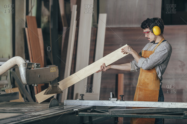 Carpenter examining plank of wood by table saw at workshop