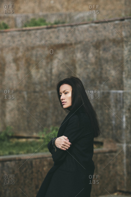 Side view of solitude woman looking away while standing arms crossed against wall