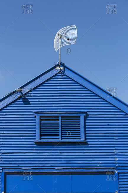 Low angle view of antenna on blue church against clear sky