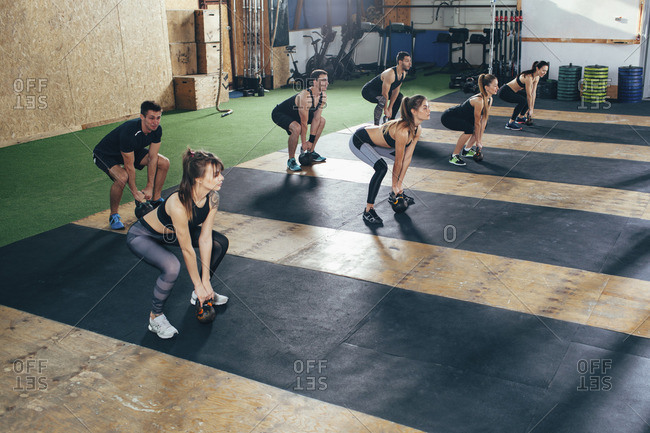 High angle view of determined athletes exercising with kettle bells at health club