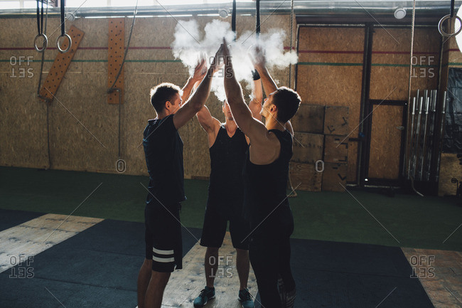Determined sportsmen dusting sports chalk together at gym
