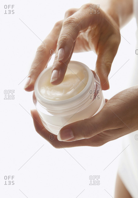 Cropped image of woman holding moisturizer container against white background