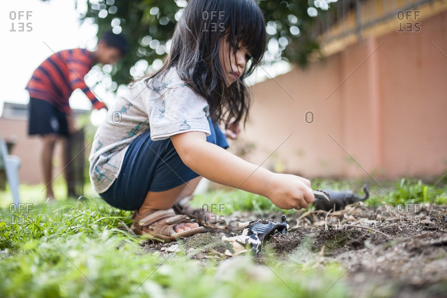 Boy playing with dinosaur toys in dirt