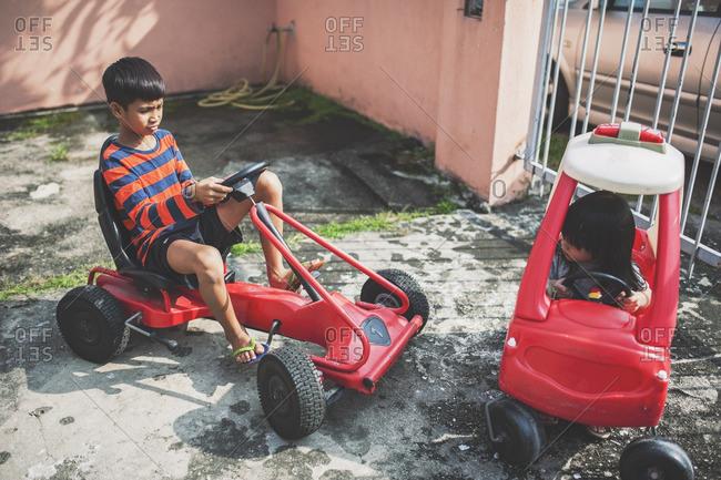 Boys riding carts around yard
