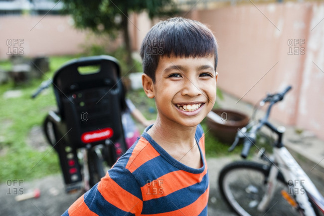 Malaysian boy smiling in yard