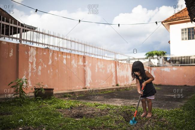 Boy digging in his backyard
