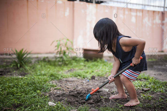 Boy digging in dirt in backyard