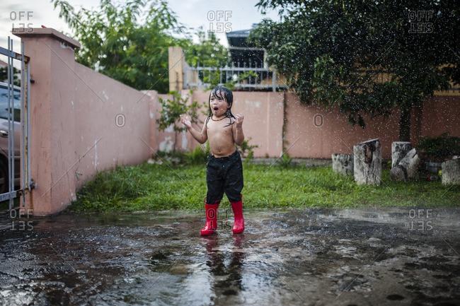 Excited boy in rain in yard
