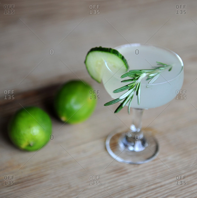 Mixed drink with rosemary and cucumber on a bar with limes
