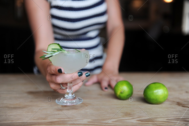 Woman holding a mixed drink with rosemary and cucumber