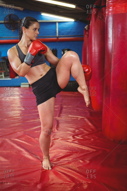 Female boxer punching a boxing bag in fitness studio