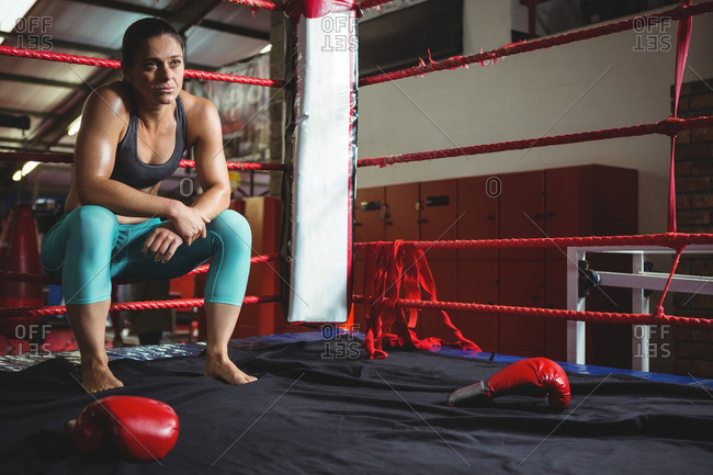 Thoughtful female boxer sitting on rope in boxing ring