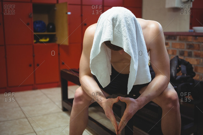 Tired boxer sitting on bench in locker room