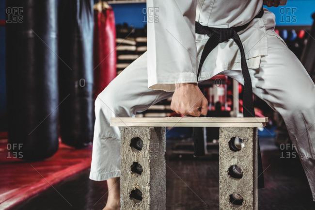 Karate player breaking wooden plank in fitness studio