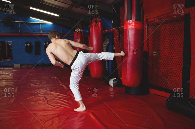 Karate player practicing kickboxing in fitness studio