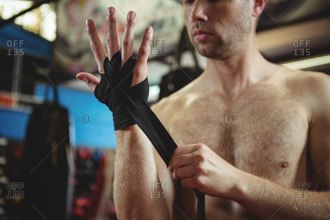 Mid section of boxer wearing black strap on wrist in fitness studio